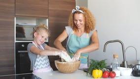 母亲和儿童获得女儿的女孩乐趣,当做晚餐在厨房时 影视素材