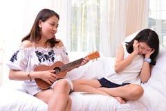 母亲和十几岁的女儿谈话在客厅 免版税库存图片