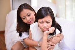 母亲和十几岁的女儿谈话在客厅 免版税库存照片