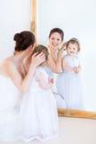 年轻母亲和卷曲女儿在镜子前面 图库摄影