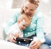 母亲和可爱的婴孩有片剂个人计算机的 图库摄影