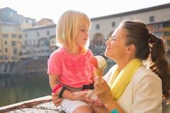 母亲和吃冰淇凌的女婴在佛罗伦萨 库存照片