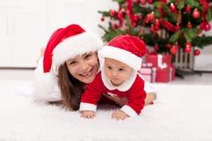 母亲和圣诞老人帽子的女婴 免版税库存图片