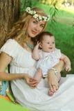 母亲和坐在树下的女婴 图库摄影