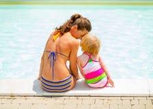 母亲和坐在游泳池附近的女婴 免版税库存照片