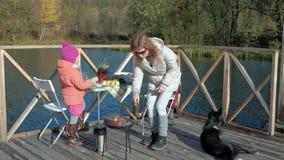 母亲和女儿、一年轻女人和一女孩衣服暖和的,准备菜和肉在格栅,使用 股票录像