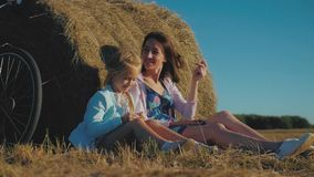 母亲和女儿一个领域的与干草堆在一个晴天 有快乐的女儿的家庭妈妈他们获得了自行车  影视素材