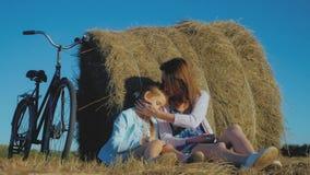 母亲和女儿一个领域的与干草堆在一个晴天 有快乐的女儿的家庭妈妈他们获得了自行车  股票视频