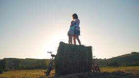 母亲和女儿一个领域的与干草堆在一个晴天 有快乐的女儿的家庭妈妈他们获得了自行车  股票录像