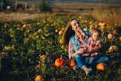 母亲和女儿一个领域的用南瓜 免版税库存图片