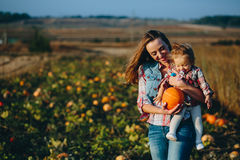 母亲和女儿一个领域的用南瓜 库存照片