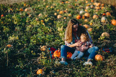 母亲和女儿一个领域的用南瓜 免版税图库摄影