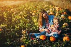 母亲和女儿一个领域的用南瓜 免版税库存照片