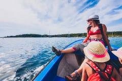母亲和女儿一条小船的在海 图库摄影