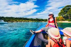 母亲和女儿一条小船的在海 库存图片