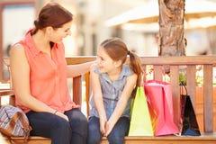 母亲和女儿一起坐在购物中心的位子 库存图片