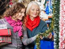 母亲和女儿买的圣诞节装饰 免版税库存照片