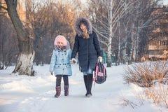 母亲和女儿从学校去 库存图片