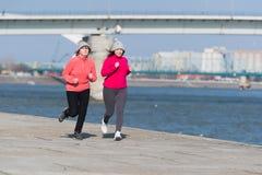 母亲和女儿佩带的运动服和赛跑在大风天 库存图片
