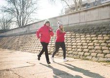 母亲和女儿佩带的运动服和赛跑在大风天 免版税库存图片