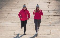母亲和女儿佩带的运动服和赛跑在大风天 库存照片