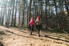 母亲和女儿佩带的运动服和赛跑在森林里在 免版税库存照片