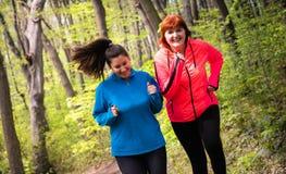 母亲和女儿佩带的运动服和赛跑在森林里 免版税库存图片