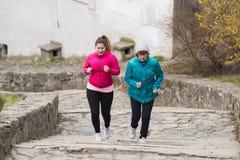 母亲和女儿佩带的运动服和赛跑在楼上在c 免版税库存图片