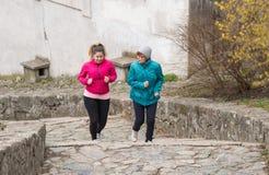 母亲和女儿佩带的运动服和赛跑在楼上在c 免版税图库摄影