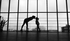 母亲和女儿剪影健身房的 亲吻 免版税库存照片