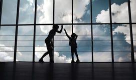 母亲和女儿剪影健身房的 免版税库存照片