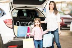 母亲和女儿包装在汽车的购物袋 库存照片