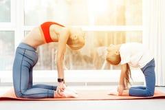 母亲和女儿参与在运动服的瑜伽 他们在有全景窗口的一间明亮的屋子 免版税图库摄影