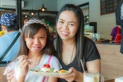 母亲和女儿吃果子乳酪蛋糕 免版税库存照片