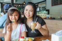 母亲和女儿吃果子乳酪蛋糕 库存图片
