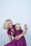 母亲和女儿同样在白色背景的演播室穿戴 图库摄影