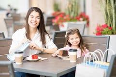 母亲和女儿咖啡馆的在做购物以后 图库摄影