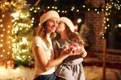 母亲和女儿圣诞老人帽子的在一间屋子里给礼物Chr的 库存图片