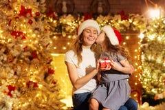 母亲和女儿圣诞老人帽子的在一间屋子里给礼物Chr的 库存照片