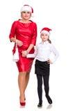 母亲和女儿圣诞老人帽子的 免版税库存照片