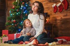 母亲和女儿在一个装饰的房子里庆祝圣诞节 免版税库存图片