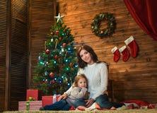母亲和女儿在一个装饰的房子里庆祝圣诞节 图库摄影