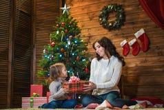 母亲和女儿在一个装饰的房子里庆祝圣诞节 免版税库存照片