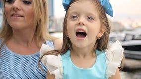 母亲和女儿在一把蓝色礼服和蓝色大弓的三年 影视素材