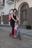 母亲和女儿在一辆滑行车乘坐在城市 免版税图库摄影