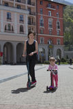 母亲和女儿在一辆滑行车乘坐在城市 免版税库存照片