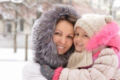 母亲和女儿在冬天 免版税库存照片