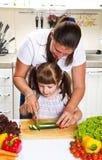 母亲和女儿在准备菜的厨房里 免版税库存照片