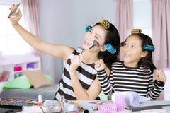 母亲和女儿在卧室拍照片 库存图片