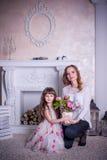 母亲和女儿在壁炉附近坐 库存图片